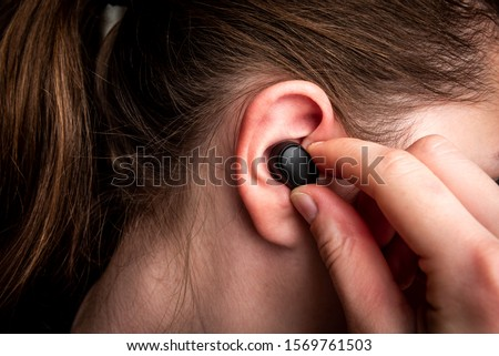 Black wireless headphones in ear. Royalty-Free Stock Photo #1569761503