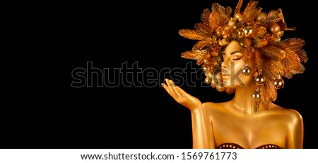 Christmas Woman. Winter girl pointing Hand, holding product. Beautiful New Year and Christmas Tree Holiday Hairstyle and gold skin Makeup. Gift. Girl in decorated Xmas wreath. Beauty Fashion Model #1569761773