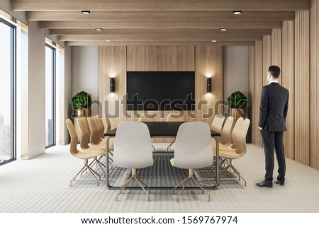 Businessman standing in modern meeting room interior with empty tv screen. Presentation and corporate concept. 3D Rendering #1569767974