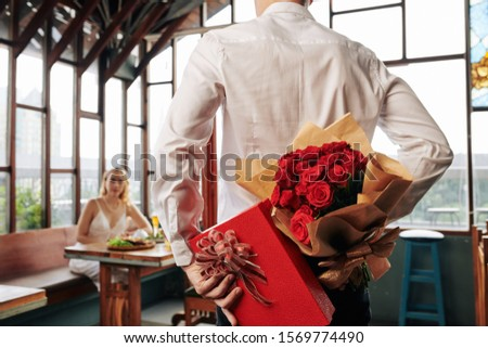 Young man hiding present and bouquet of flowers behind his back when coming to date with girlfriend in restaurant #1569774490