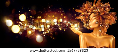 Christmas Wish. Winter Woman with Magic in Her Hand. Beautiful New Year and Christmas Tree Holiday Hairstyle and gold skin Makeup. Gift. Girl in Xmas wreath. Beauty Fashion Model Holiday Background #1569789823