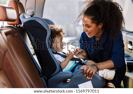 Happy mother looking at her son in a baby seat. Young female preparing kid for a trip. Royalty-Free Stock Photo #1569797011