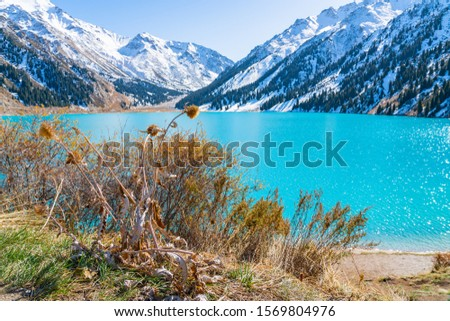 Lake with turquoise water surrounded by a mountain massif. Big Almaty lake in the mountains. Kazakhstan  #1569804976