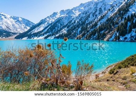 Lake with turquoise water surrounded by a mountain massif. Big Almaty lake in the mountains. Kazakhstan  #1569805015