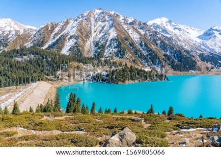 Lake with turquoise water surrounded by a mountain massif. Big Almaty lake in the mountains. Kazakhstan  #1569805066