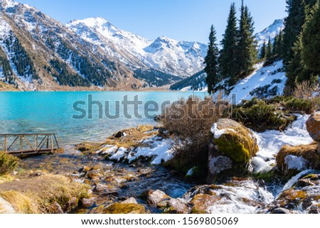 Lake with turquoise water surrounded by a mountain massif. Big Almaty lake in the mountains. Kazakhstan  #1569805069