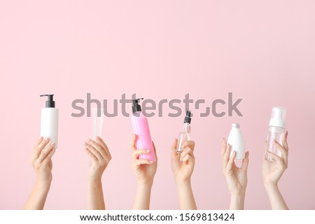 Female hands with different cosmetic products in bottles on color background #1569813424