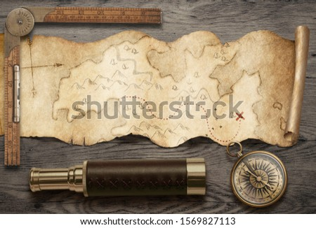 Old torn treasure map with compass and spyglass top view still life. Adventure and travel concept. Mixed media. #1569827113