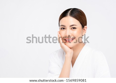 Beauty shot of youthful bright skin pretty Asian woman with hand touching face on white background #1569859081