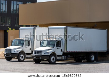 Small compact commercial industrial grade professional rigs semi trucks with long box trailers standing in warehouse dock loading different cargo for next timely delivery #1569870862