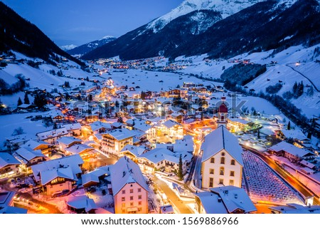 Winter night cityscape in the Austrian town of Neustift. Aerial view of the town center and the church. Night illumination of houses and traffic light. Tyrol, Stubai Valley #1569886966