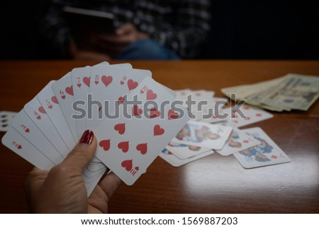 Gamble cards in woman hand with group of cards and money on wooden table with man sitting in the dark room background. #1569887203