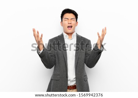 young chinese man furiously screaming, feeling stressed and annoyed with hands up in the air saying why me against flat color wall #1569942376