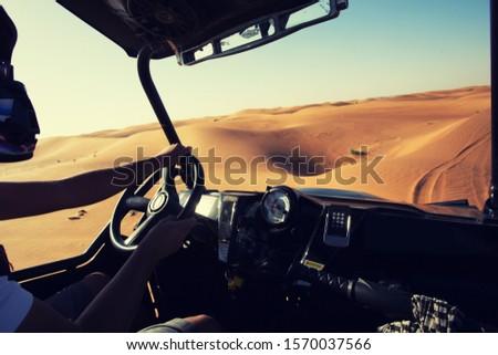 Driving quad buggy car at desert dunes at Al Awir near Dubai, inside vehicle view #1570037566
