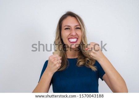 Caucasian young woman rejoicing her success and victory clenching her fists with joy. Lucky woman with hat being happy to achieve her aim and goals.Positive emotions, feelings. #1570043188