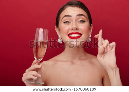 Image of a young nervous pleased woman with bright red lipstick isolated over red wall background holding glass with champagne or wine showing hopeful please gesture fingers crossed. #1570060189