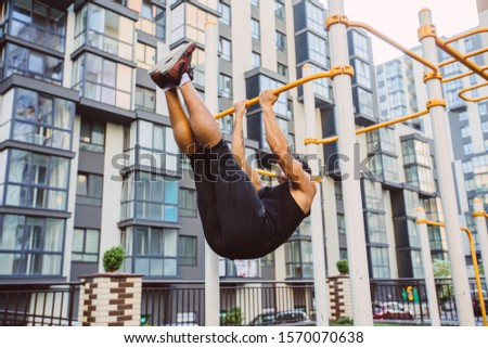 Workout, sportsman pull ups the horizontal bar with big effort. Fitness mixed race man doing workouts in morning on street sports ground outdoors on urban background. Cityscape view #1570070638