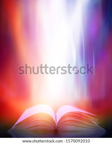 Imagine a picture book of an ancient book opened on a wooden table with a sparkling golden background. With magical power, magic, lightning around a glowing glowing book In the room of darkness #1570092010