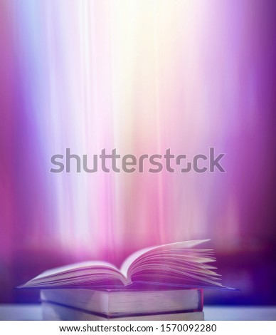 An ancient book that opens with magic, the magic light in the darkness on the wooden table, by the bright light shining down as the power to search for knowledge, religion and background #1570092280