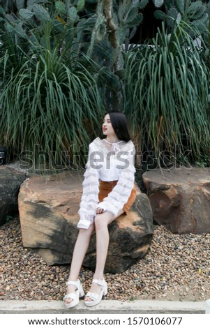 Portrait of young asian woman posting in cactus and succulent garden