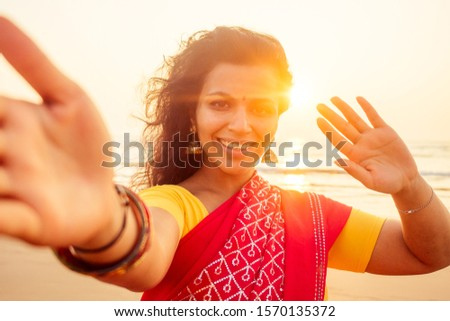 self portrait of gorgeous beautiful indian woman taking selfie photo with mobile phone camera in exotic tropical beach enjoying summer Goa beaches.