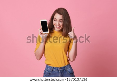 Portrait of happy young woman showing at blank screen mobile phone and hand gesture good isolated over pink background. #1570137136