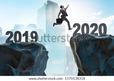 Businessman jumping from year 2019 to 2020 #1570138318