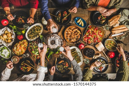 Traditional Turkish celebration dinner. Flat-lay of peopleeating Turkish salads, cooked vegetables, meze starters, pastries and drinking raki drink, top view. Middle Eastern cuisine #1570144375