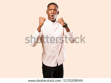young african american black man celebrating an unbelievable success like a winner, looking excited and happy saying take that! against beige wall #1570208044