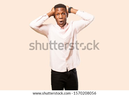 young african american black man looking excited and surprised, open-mouthed with both hands on head, feeling like a lucky winner against beige wall #1570208056