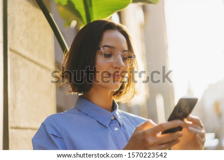 Happy woman with beautiful smile chatting on cell smartphone outdoors, Business woman in styling glasses and blue shirt using smartphone on the street #1570223542