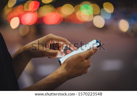 Cropped view of male fingers typing text message on blank display of modern smartphone on bokeh background. Man's hands holding mobile phone and chatting online in social networks