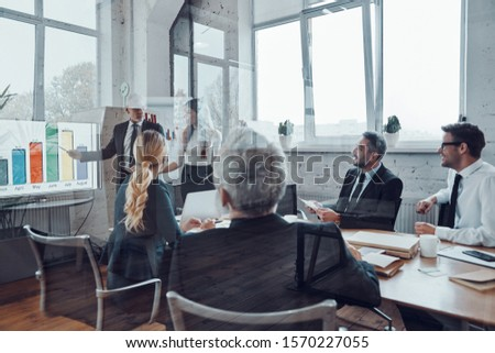 Modern businessman conducting presentation and analyzing data on the graph while having staff meeting in the board room                 #1570227055