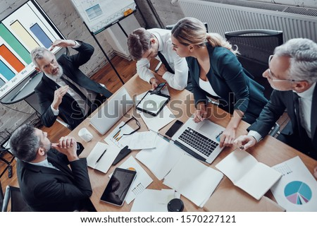 Top view of coworkers in elegant formalwear discussing business risks while working in the modern office #1570227121