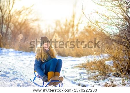 Cute girl sledding in a snowy winter park. Children have fun and have fun. Winter fun. #1570227238