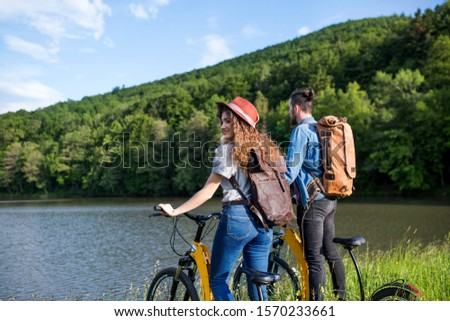Young tourist couple with electric scooters in nature, standing by lake. #1570233661