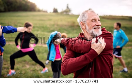 Large group of fit and active people doing exercise in nature, stretching. Royalty-Free Stock Photo #1570237741
