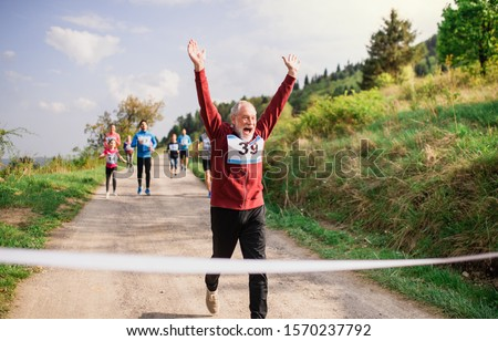 Senior man runner crossing finish line in a race competition in nature. #1570237792