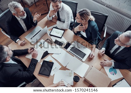 Top view of coworkers in elegant formalwear discussing business risks while working in the modern office                 #1570241146