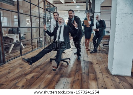 Playful businessmen pushing their boss on the office chair while running in the hallway              Royalty-Free Stock Photo #1570241254