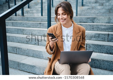 Young cheerful styliah businesswoman in coat with laptop happily happily using cellphone on stairs on street Royalty-Free Stock Photo #1570308568