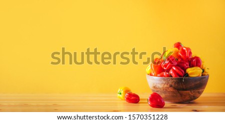 Colorful scotch bonnet chili peppers in wooden bowl over orange background. Copy space Royalty-Free Stock Photo #1570351228