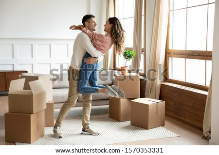 Happy young husband lifting excited wife celebrating moving day with cardboard boxes, proud overjoyed family couple first time home buyers renters owners having fun enjoy relocation, mortgage concept #1570353331
