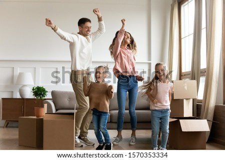 Funny happy family young parents and cute little kids children daughters dancing in living room jump together having fun celebrating moving day relocating in new home renovating apartment with boxes #1570353334