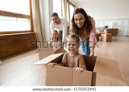 Happy parents playing with cute small kids daughters laughing on moving day, family tenants renters homeowners and children girls having fun riding in box in living room relocating new home concept #1570353442