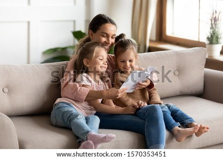 Happy family young mother babysitter hold read book relax embrace cute little children daughters, smiling parent mum tell small kids funny fairy tale story sit on sofa having fun together at home #1570353451