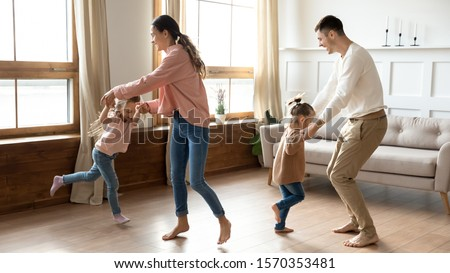 Happy active family young mom dad and cute little children daughters holding hands dancing together in living room interior, carefree funny small kids having fun jumping laughing with parents at home #1570353481