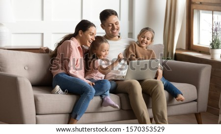 Cheerful family parents mum dad and little children daughters bonding using laptop having fun together watching cartoons online make internet shopping looking at computer screen sit on sofa at home #1570353529