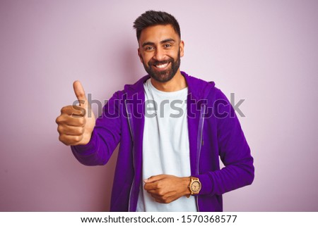 Young indian man wearing purple sweatshirt standing over isolated pink background Looking proud, smiling doing thumbs up gesture to the side #1570368577