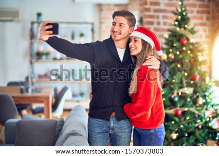 Young beautiful couple smiling happy and confident. Standing and hugging make selfie by camera around christmas tree at home #1570373803